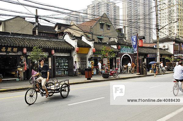 Straße im alten Shanghai  kleine Läden  Kabelchaos  Fahrradrikscha  neue Wohnsilos  Shanghai  China  Asien