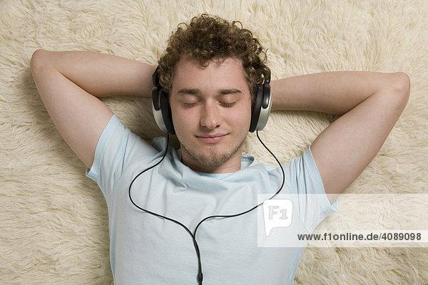 Junger Mann mit Kopfhörer  Musik hörend