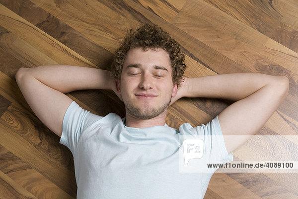 Junger Mann auf Fußboden liegend  entspannend