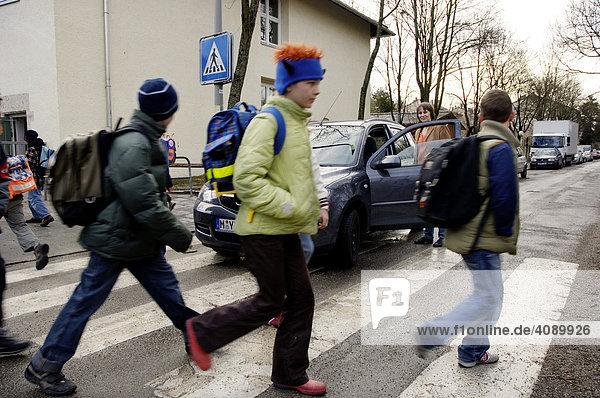 Schulkinder laufen über Zebrastreifen  Auto parkt gefährlich