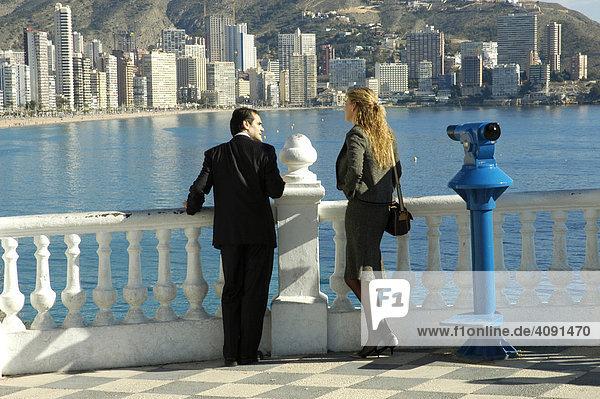Mann und Frau in Geschaeftskleidung an einem Aussichtspunkt mit Blick auf den Playa de Levante  Benidorm  Costa Blanca  Spanien