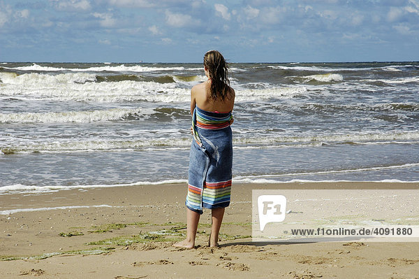 Woman wrapped in a towel is looking out at the sea  Katwijk aan Zee  South Holland  Holland  The Netherlands