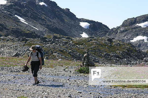 Woman crosses a stream with her shoes off Chilkoot Trail British Columbia Canada