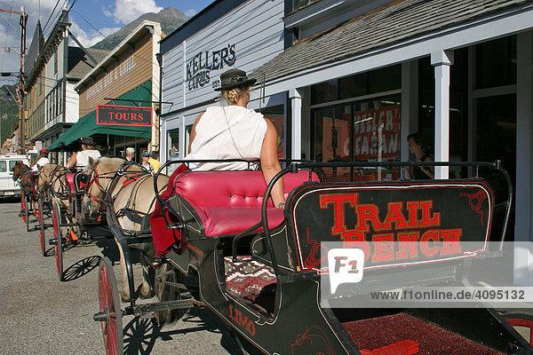 Pferdekutschen transportieren Touristen durch die Goldrauschstadt von Skagway Alaska USA