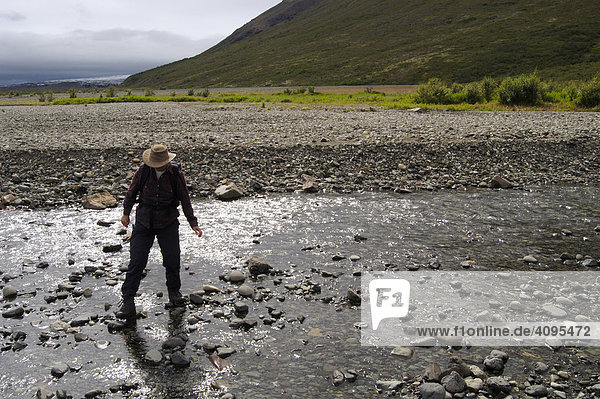 Woman crossing a river Skaftafell National Park Iceland