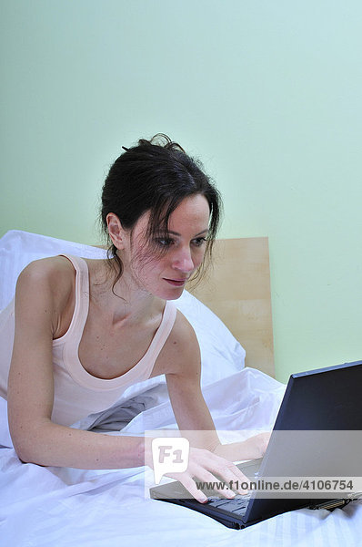 Portrait of a Caucasian adult woman  alone with laptop in the bed of the sleeping room