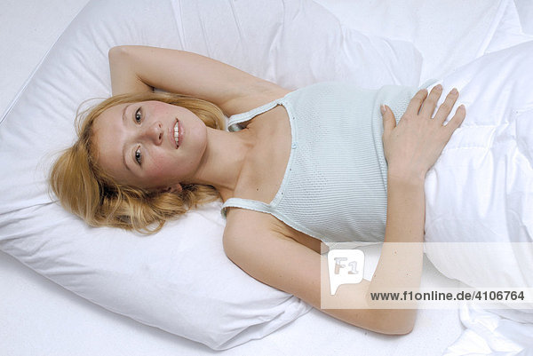 Porträt einer blonden  jungen Frau  liegt alleine im Bett