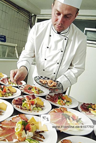 Chef preparing appetiser dishes in restaurant kitchen