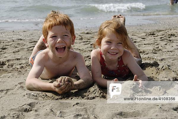 Zwei Kinder liegen am Strand im Wasser und freuen sich