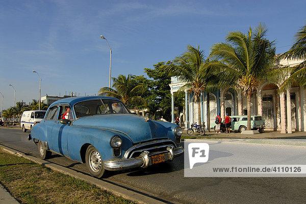 Alter amerikanischer Schlitten (Oldtimer) mit Palmen und kolonialen Gebäuden am Malecon  Cienfuegos  Kuba