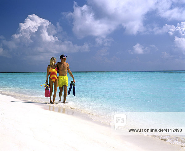 Young couple with snorkeling gear walking in shallow water  sandy beach  Maldives  Indian Ocean