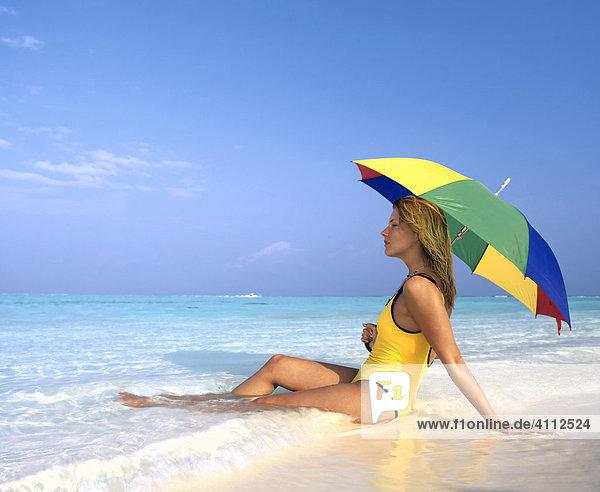 Junge Frau liegt im seichten Wasser  Strand  Sonnenschirm  Meer  Malediven