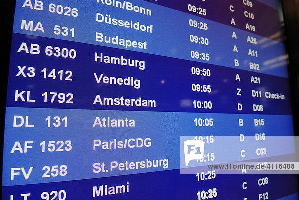 Monitor mit Liste von Flügen und Städtenamen im Abflugterminal eines Flughafens