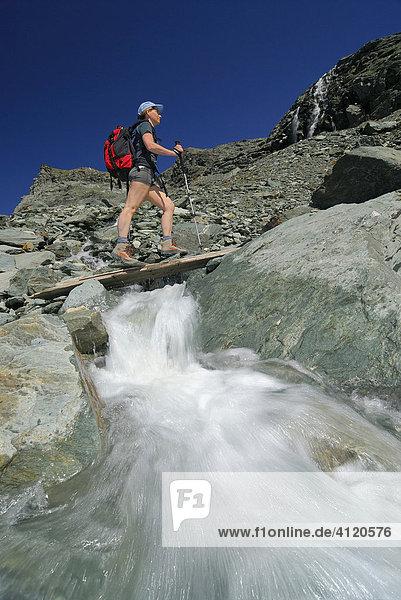 Bergwanderer  überquert eine Holzbrücke über einem Bergbach  Nationalpark Hohe Tauern  Tirol  Österreich