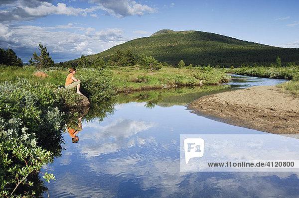 Frau sitzt an einem Fluss  Jotunheimen Nationalpark  Norwegen  Skandinavien