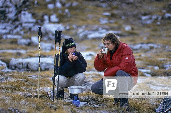 Ein Mann und eine Frau  Bergwanderer  trinken Tee  vorne ein Gaskocher mit aufgestelltem Topf  Tirol  Österreich  Europa