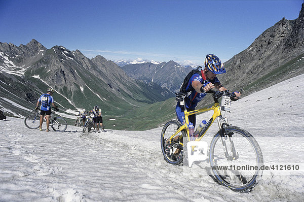 Mountain bike racers crossing a snow-covered mountain pass trail  Adidas Bike Transalp Challenge  Pfunderer Joch  Bolzano-Bozen  Italy  Europe