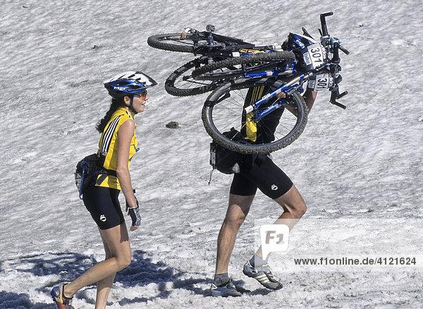 Zwei Teilnehmer der Adidas Bike Transalp Challenge  Mountainbikerennen  Mann trägt zwei Räder auf den Schultern  Frau mit gelbem Trikot und Helm geht lächelnd daneben her  Südtirol  Italien  Europa