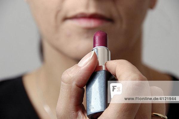 Frau beim Auftragen von Lippenstift
