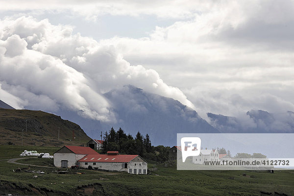 Farm and cloud covered mountains on the southern coast of Iceland  Atlantic Ocean
