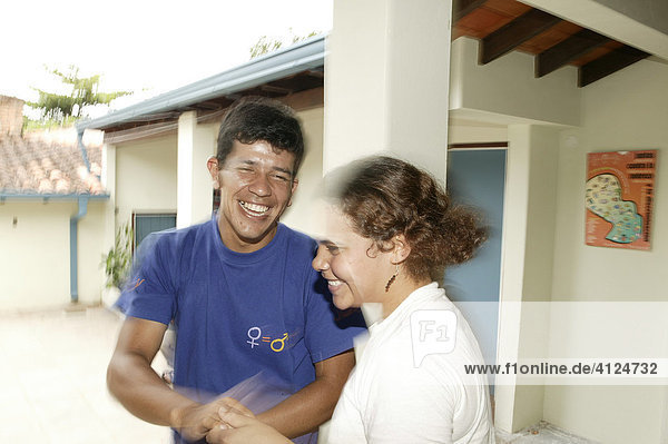 Junge Frau und Mann tanzen ausgelassen vor dem Haus  Asuncion  Paraguay  Südamerika