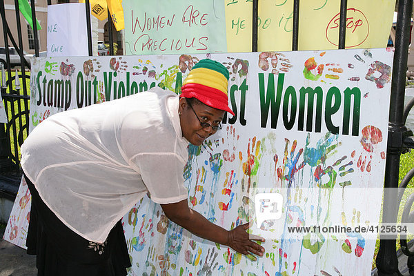 Multi-coloured handprints as a symbol of cooperation between people of various ethnic backgrounds during a protest against violence against women in Georgetown  Guyana  South America