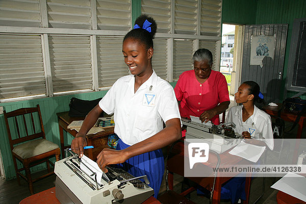 Girls wearing school uniforms in typing class at a training centre for young women in New Amsterdam  Guyana  South America