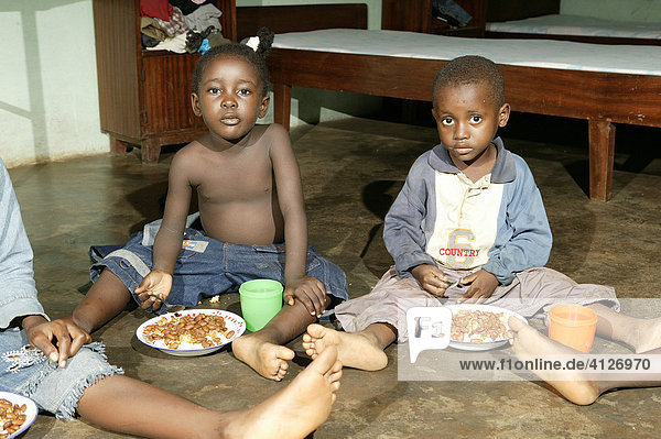 Children sitting on the floor eating their meal  at an AIDS / HIV orphanage in Douala  Cameroon  Africa