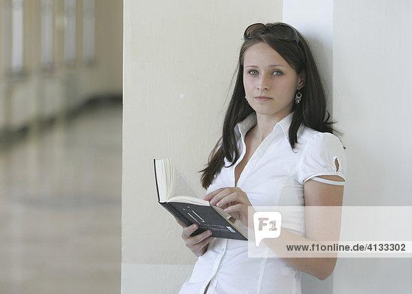 Junge Frau in der Uni mit einem Buch