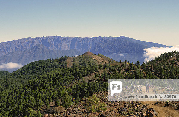 A couple of hikers on the ruta de los volcanes with the edge of the Caldera (crater) de Taburiente at the back  La Palma  Canary Islands  Spain