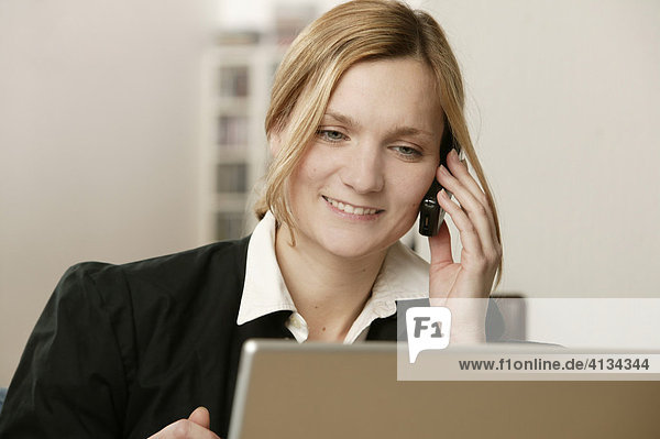 Junge blonde Frau telefoniert  am Laptop  lächelt