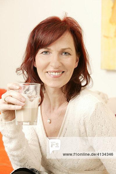 Rothaarige Frau im mittleren Alter trinkt Cappucino  lächelt