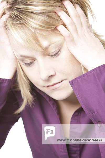 Blonde woman wearing a purple shirt  her head leaning on her hands  eyes closed