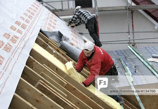 Dachdecker bringen Dämmstoff unter der Dachfolie an  Essen  Nordrhein-Westfalen  Deutschland