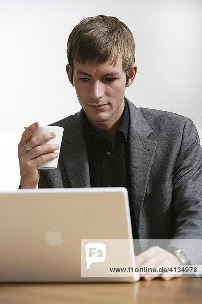 DEU  Bundesrepublik Deutschland : Junger Mann arbeitet an einen Laptop Computer  Apple.