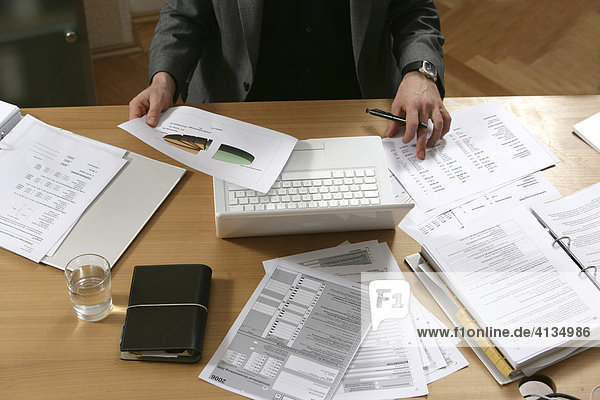 DEU  Germany : Man works in an office  at a desk