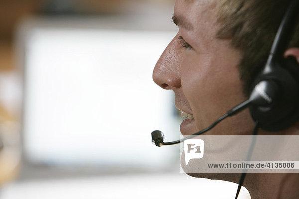DEU  Bundesrepublik Deutschland : Mann telefoniert mit Headset  Kopfhörer  Hörsprechgarnitur vor Computerbildschirm