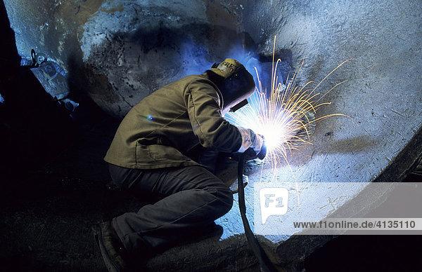 DEU Bundesrepublik Deutschland Duisburg : Schweisser in einem Stahlwerk repariert eine grosse Transportpfanne fuer fluessiges Metal. DEU Bundesrepublik Deutschland Duisburg : Schweisser in einem Stahlwerk repariert eine grosse Transportpfanne fuer fluessiges Metal.