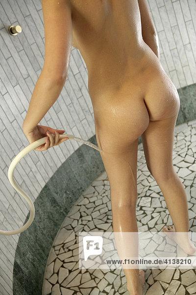 AUT  Oesterreich  Neustift-Milders  Stubaital: Wellness. Junge Frau in einem Spa  Wellnessbereich. Abkuehlen nach der Sauna. Kalt abduschen. Wellnesshotel Milderer Hof.