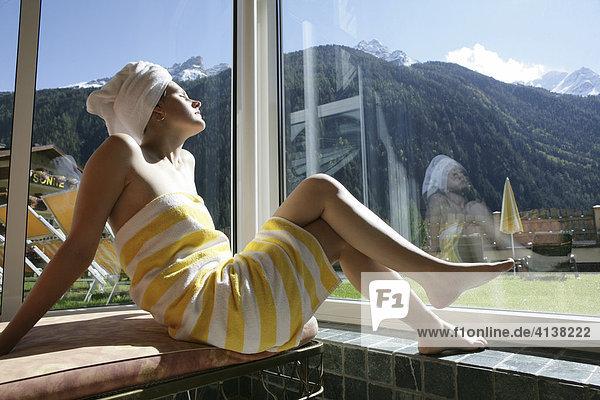 AUT  Oesterreich  Neustift-Milders  Stubaital: Wellness. Junge Frau in einem Spa  Wellnessbereich. Entspannen nach einer Wellnessanwendung im Ruhebereich. Sonnenbad. Wellnesshotel Milderer Hof.