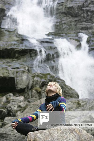 AUT  Oesterreich  Neustift  Stubaital: Alpen- Wellness. Gesundes inhalieren von feinem Wasserspray an einem Wasserfall. Das fein zuerstaeubte Wasser in der Naehe des Wasserfalls soll eine positive Wirkung auf die Atemorgane haben.