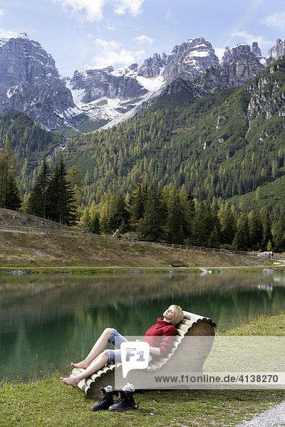 AUT  Oesterreich  Fulpmes  Stubaital: Alpen- Wellness. Erlebnisweg bei der Schlickeralm. Im Wald  am Waxeck  koennen Wanderer am Speichersee entspannen  Holzliegen und Stuehle stehen am idyllisch gelegen See  mit Alpenpanorama.