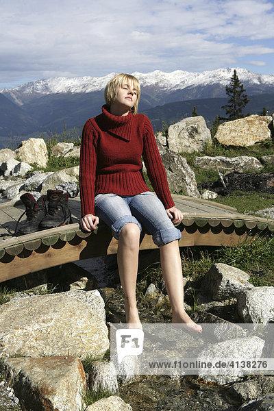 AUT  Oesterreich  Fulpmes  Stubaital: Alpen- Wellness. Erlebnisweg bei der Schlickeralm. Im Wald  am Waxeck  koennen Wanderer am Speichersee entspannen  Fussbad im einem Bergbach. See  mit Alpenpanorama.