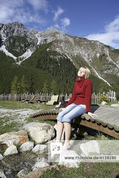 AUT,  Oesterreich,  Fulpmes,  Stubaital: Alpen- Wellness. Erlebnisweg bei der Schlickeralm. Im Wald,  am Waxeck,  koennen Wanderer am Speichersee entspannen,  Fussbad im einem Bergbach. See,  mit Alpenpanorama.