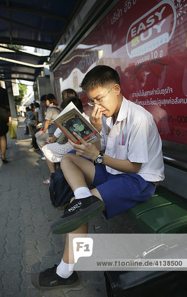 THA Thailand Bangkok Young boy waits for the bus reading a book