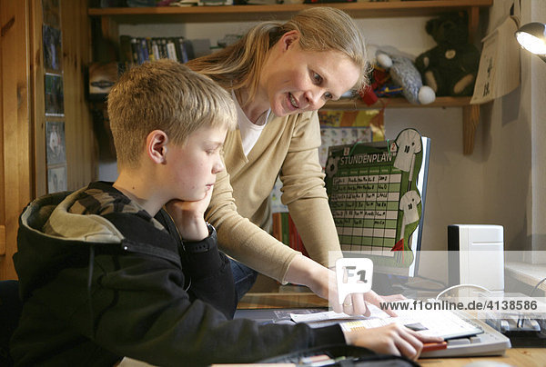 DEU  Germany: Mother is helping her son with homework for school.