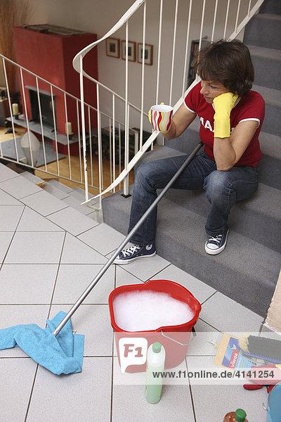 Haushalt  Frau macht eine Kaffeepause beim Hausputz