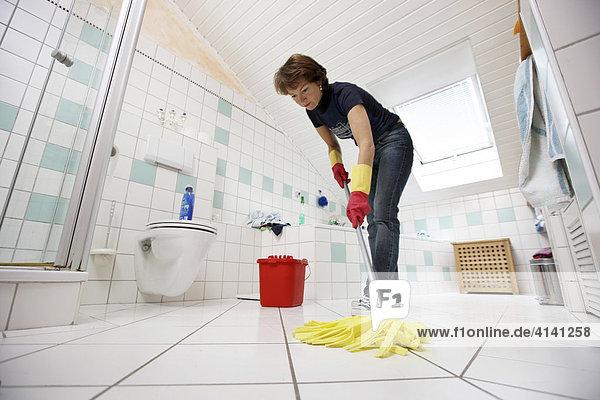 Haushalt  Frau putzt im Badezimmer