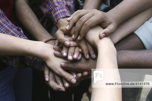 Indische und deutsche Hände  freundschaftlich aufeinandergelegt