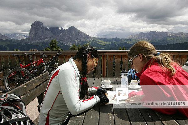 Mountainbike-Fahrerinnen bei einer Rast am Bergbahn-Restaurant Raschötz mit Marmolada  Langkofel  Plattkofel und Rosengarten im Hintergrund  Dolomiten  Italien
